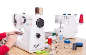 Woman seamstress work on the sewing products. On a white background.